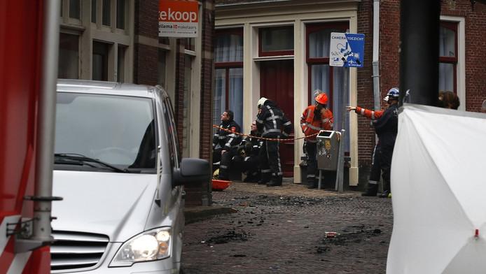 Een lijkwagen (links) verlaat met het stoffelijk overschot van een slachtoffer de plek van de brand in Leeuwarden.