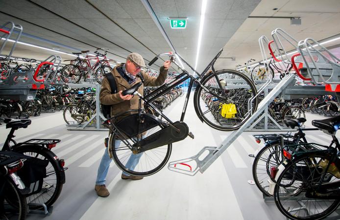 Aad Schouten (55) uit Delft parkeert zijn fiets in de nieuwe ondergrondse fietsenstalling onder het station in Delft.