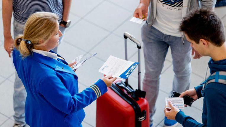Werknemers van KLM delen flyers uit aan reizigers op Schiphol. Beeld anp