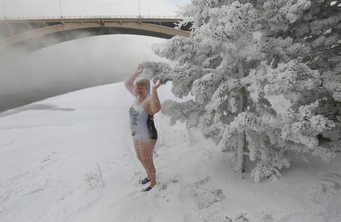 De Russische Lyubov Valiyeva, lid van de plaatselijke ijszwemclub, besprenkelt zichzelf met sneeuw van een dennenboom op de oever van de Yenisei rivier, bij een temperatuur van zo'n 38 graden onder nul in Krasnojarsk. Foto Ilya Naymushin