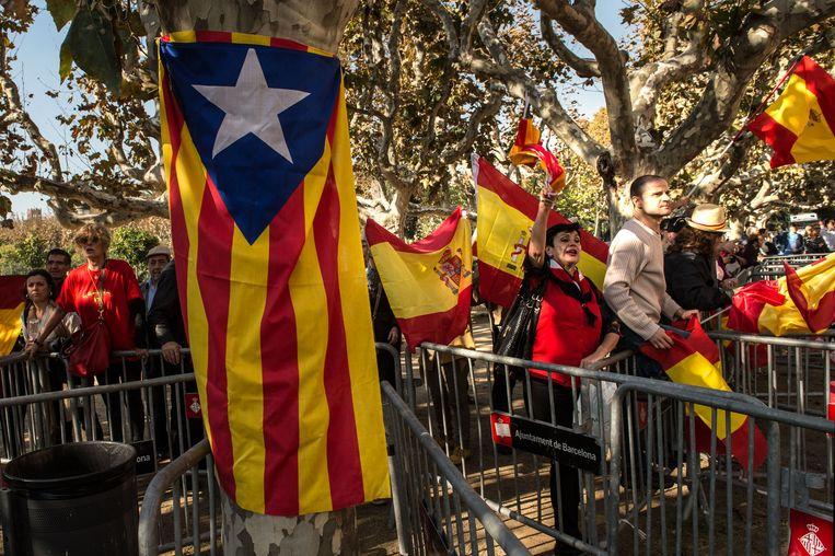 Mensen zwaaien met Spaanse vlaggen naast de onafhankelijkheidsvlag van de Catalanen. Beeld getty