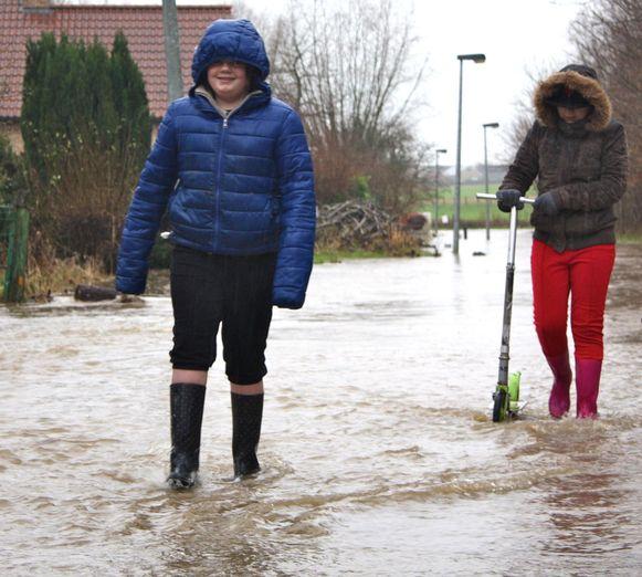 Twee meisjes wagen zich door het water.
