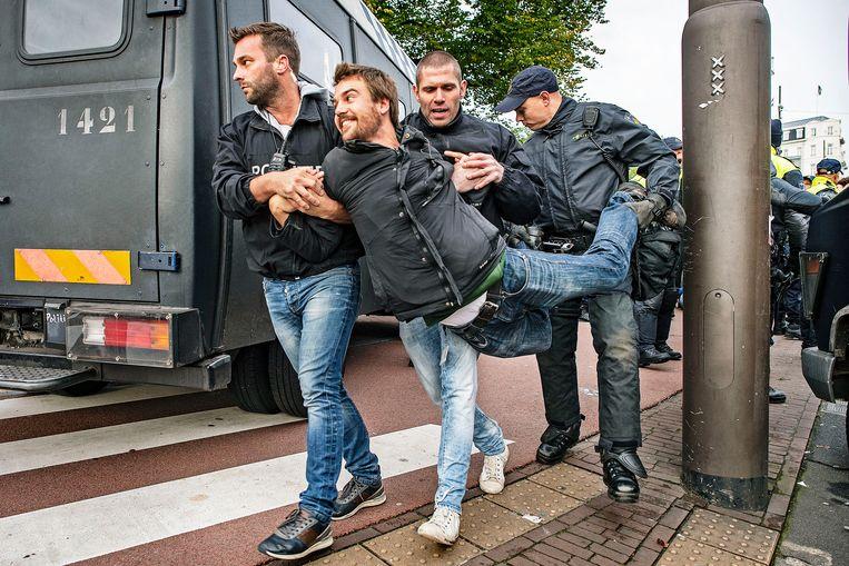 Een voor een worden de actievoerders opgepakt en afgevoerd.  Beeld Guus Dubbelman / de Volkskrant