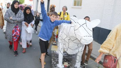 Bonte stoet met koe en kameel steekt stadsring over