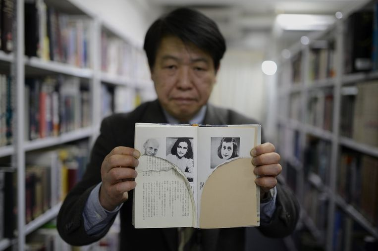 Japanse bibliothecaris Kotaro Fujimaki met een gescheurd exemplaat Beeld AFP
