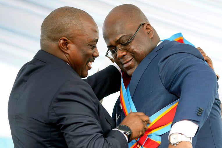 Inhuldiging Congolese President Felix Tshisekedi. Hij krijgt de presidentiële sjerp omgehangen door vertrekkend president Joseph Kabila.  Beeld AP Photo/Jerome Dela