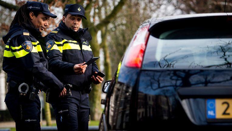 Angenten controleren de papieren van een automobilist Beeld null