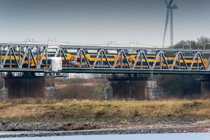 Met doek worden de mensen tegen het weer beschermd bij het werk aan de spoorbrug over de Waal bij Zaltbommel.