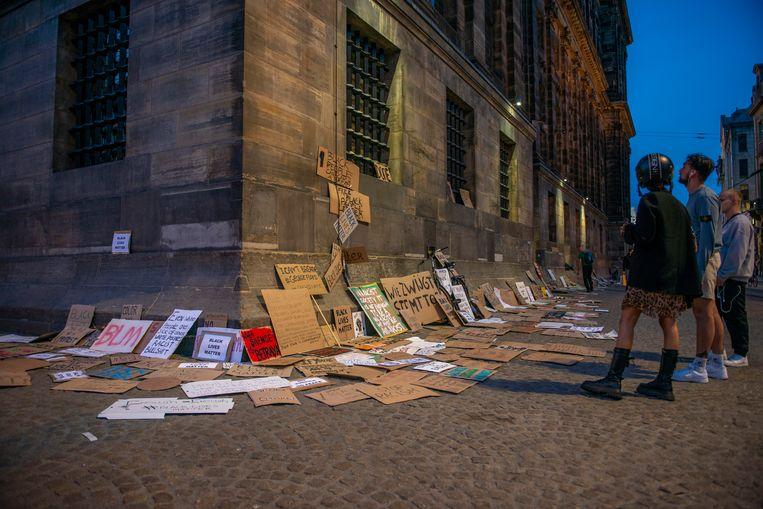 Achtergelaten demonstratieborden staan als stille getuigen tegen het Paleis op de Dam, na afloop van het antiracismeprotest. Beeld Hollandse Hoogte / Friso Spoelstra