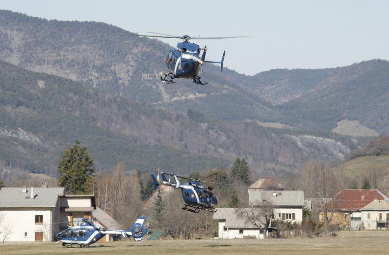 Reddingshelikopters vliegen af en aan naar het rampgebied. Beeld ap
