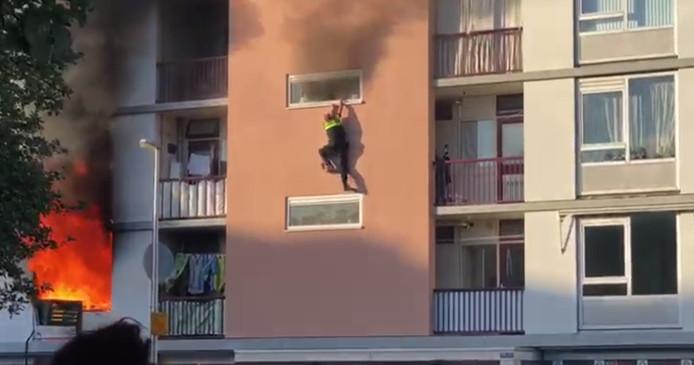 Agent Zefanja Engberts hangt uit het raam van de brandende flat in Kanaleneiland.