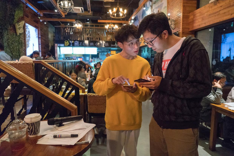 Jiang Jing (rechts) is namens het bedrijf Jiaoda Matchmaking de organisator van deze speeddate voor hoogopgeleide singles in Shanghai.  Beeld Ruben Lundgren