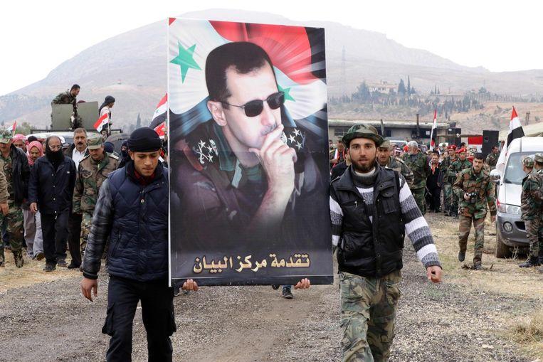 Syrische mannen houden het portret vast van president Bashar al-Assad, aan het einde van een paramilitaire training onder leiding van het Syrische leger in al-Qatif, op 22 februari. Beeld afp
