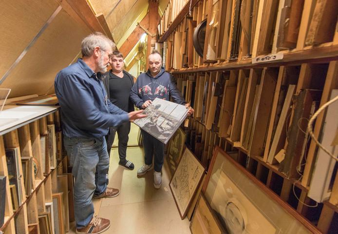 Museumvrijwilliger Ton Bruyns leidt een paar bezoekers rond in het schilderijendepot in de nok van het museum.