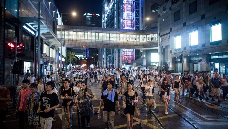 Demonstranten trekken door een centraal gelegen straat in Hongkong. Beeld afp