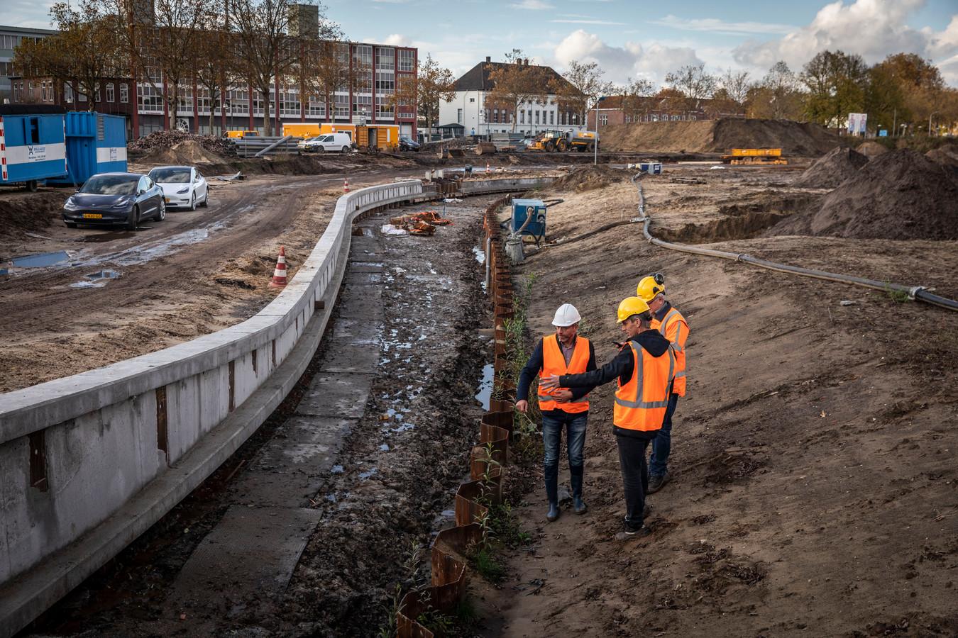 Wethouder Erik de Vries (links), projectleider Jack Vogels van de gemeente en aannemer Ad van den Hurk maken een rondje door het Burgemeester Geukerspark in aanleg. Op de achtergrond is Raymakers aan het kanaal zichtbaar.