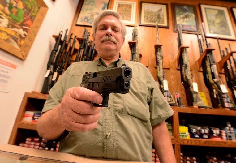 Wapenverkoper Bob Croy met een Sig Sauer 9mm handwapen (Archiefbeeld).