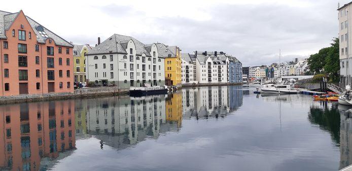 De gekleurde gevels van de woningen in de haven van het Noorse Alesund weerspiegelen in het water. Een mooi rustmoment tijdens een cruise.