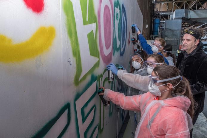 Kunstenaar Gerry Jilesen begeleid kinderen die een graffiti kunstwerk maken.