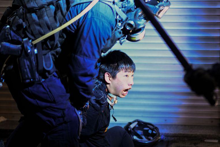 Een demonstrant wordt door een agent vastgehouden in Hongkong.