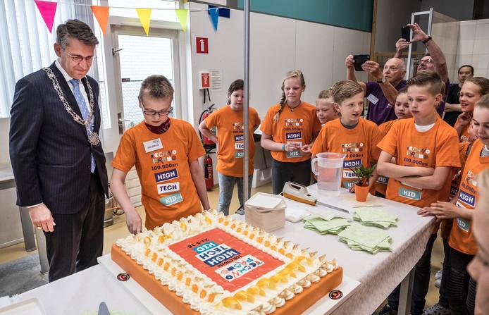 Luuk Teunissen snijdt de taart aan. Zijn schoolgenoten en burgemeester Wim Hillenaar van Cuijk kijken toe.
