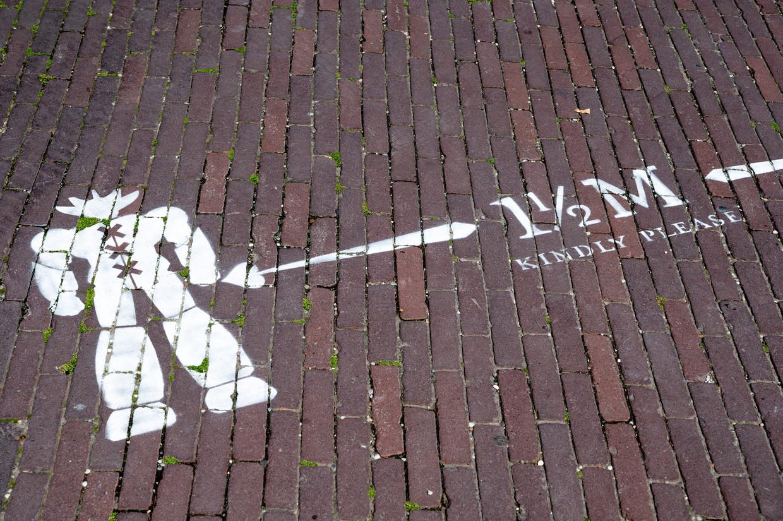 Een opschrift op een Amsterdamse straat maant mensen om afstand te houden.