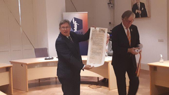 Burgemeester Rensen toont het smeekschrift met handtekeningen.