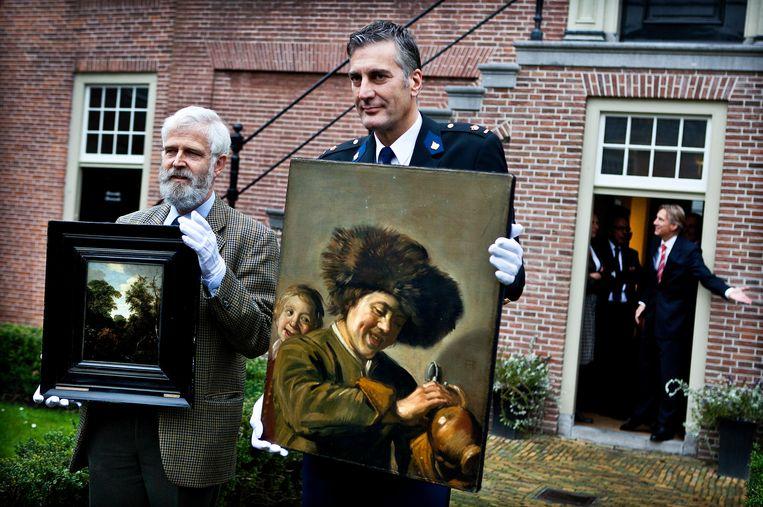 In 2001 tonen de directeur van het museum Het Hofje van Mevrouw van Aerden en de districtchef Alblasserwaard de teruggevonden schilderijen van Frans Hals en Jacob van Ruysdael. Beeld Hollandse Hoogte /  ANP