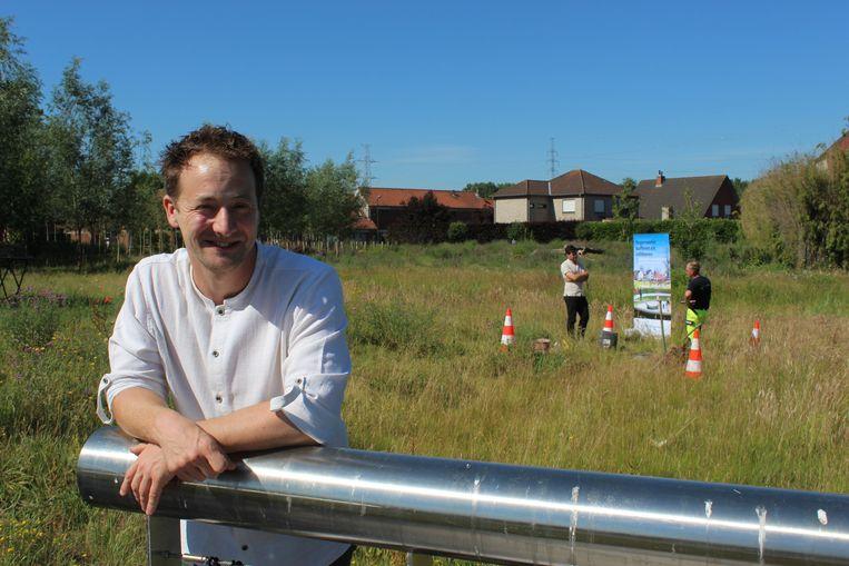 Een trotse schepen Bob D'Haeseleer in het Wilgenpark in Eeklo, terwijl experten op de achtergrond de grondwaterstand opmeten.