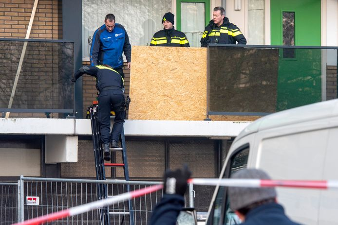 Een agent klimt op een trap om in de flat aan het Gelderseplein te komen. De ingang van de flat moet zo min mogelijk gebruikt worden om sporen veilig te stellen voor het politie onderzoek.