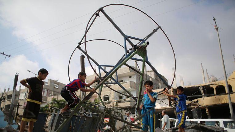 Palestijnse kinderen spelen bij een vernield reuzenrad Beeld afp