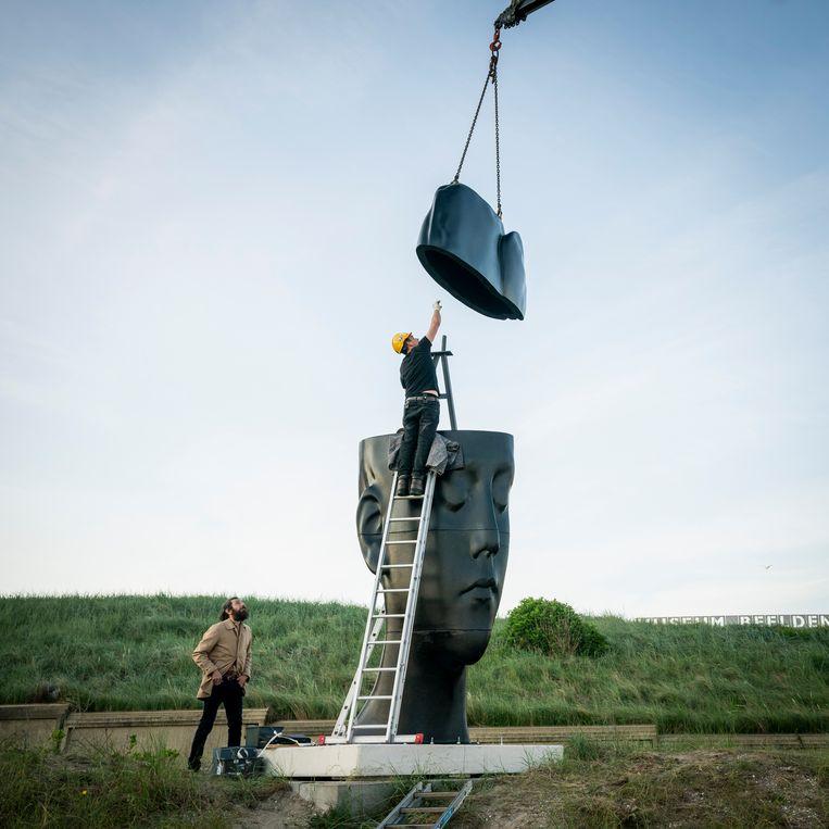 Jaume Plensa kijkt toe hoe een beeld van hem wordt geplaatst voor zijn tentoonstelling in het museum Beelden aan Zee. Beeld Foto Martijn Beekman