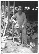 De Rooi Harten: een pater stopt met houtakken en poseert met zijn bijl. De foto is in 1930 gemaakt op de Kei-eilanden in Indonesië.