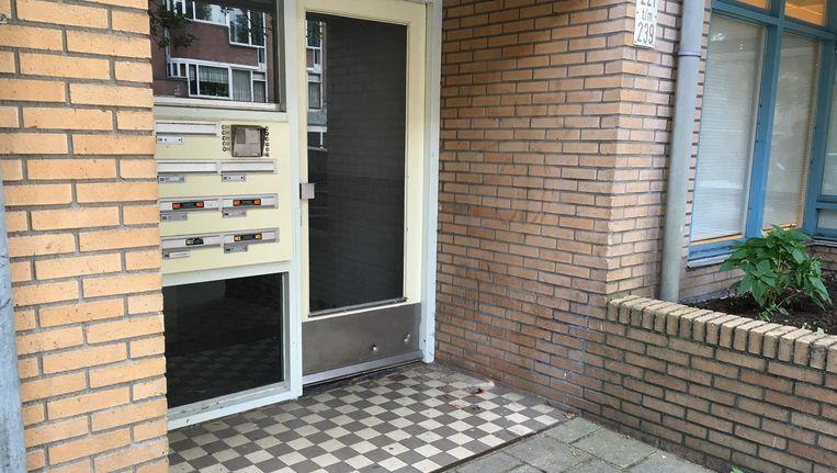Het schietincident vond plaats voor het portiek van een flat. In de deur zijn meerdere afdrukken van kogels te zien. Beeld Maarten van Dun