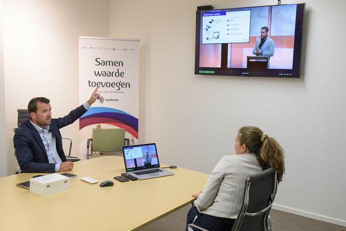 Martin Landkroon (Rabobank) en Sophia de Rooij, bestuursvoorzitter MST, kijken naar de presentatie van Pepijn Beekman van ECsens.