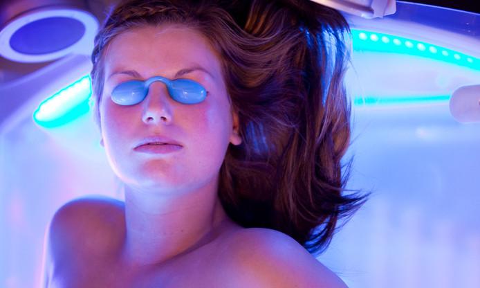 Een meisje ligt met een beschermend brilletje onder een zonnebank.