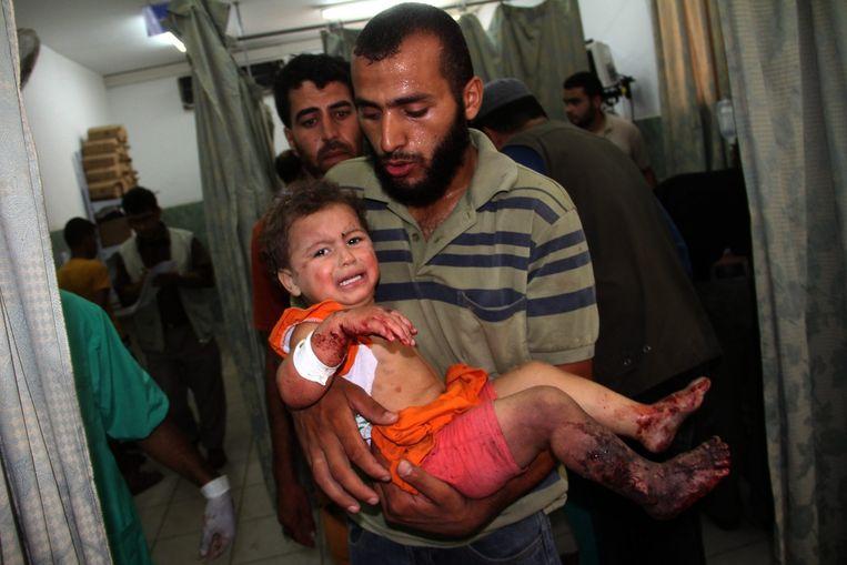 Een Palestijnse man draagt een gewond kind naar het ziekenhuis na beschietingen in de stad Rafah. Beeld epa