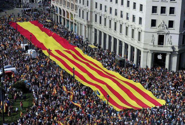 Betogers houden een Spaanse en een Catalaanse vlag omhoog tijdens een demonstratie in Barcelona in het kader van de onafhankelijkheid van Catalonië. Beeld afp