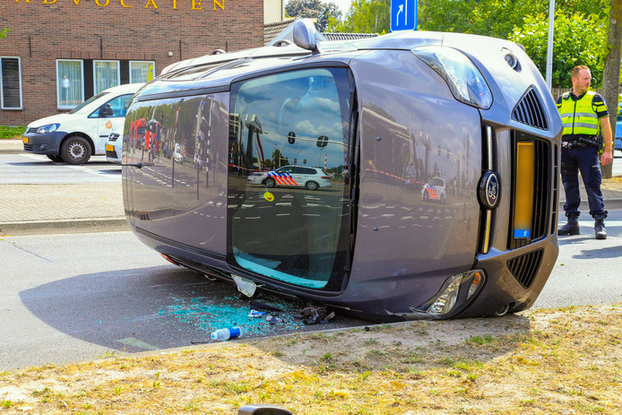 Auto op zijkant na aanrijding met andere auto en verkeerslicht in Helmond.