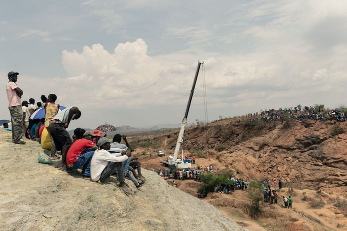 Toeschouwers kijken toe op de reddingswerkers.