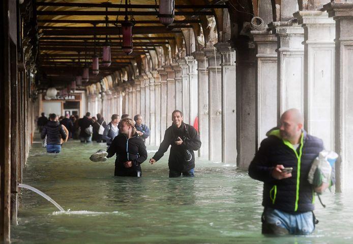 Toeristen waden door het water op het ondergelopen San Marco-plein.