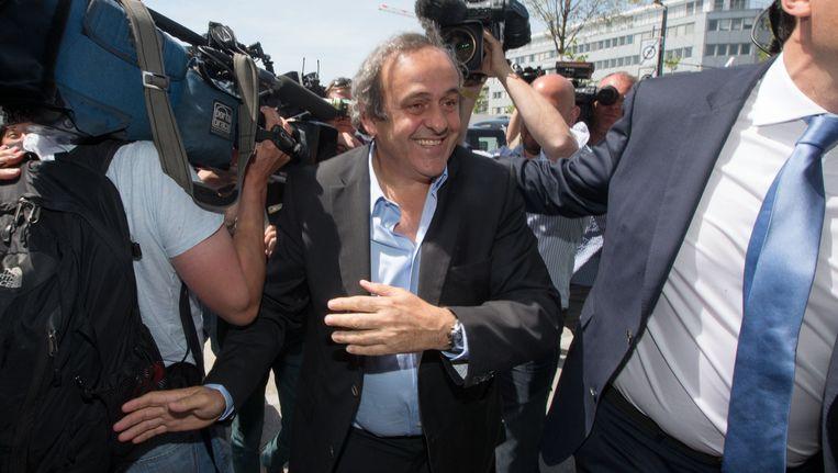 UEFA-voorzitter Michel Platini baant zich een weg tussen cameraploegen. Beeld getty