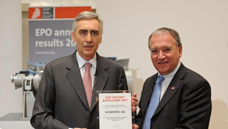Benoît Battistelli op rechts in 2011, wanneer hij een certificaat aan de SEO van Siemens uitreikt. Beeld epa