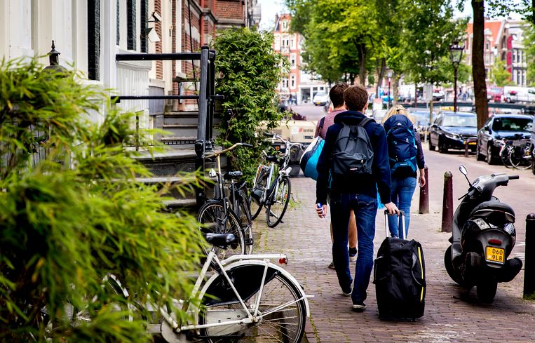 Toeristen op de grachten in Amsterdam. Rolkoffers zijn één van de overlastproblemen door de toenemende populariteit van AirBnB.