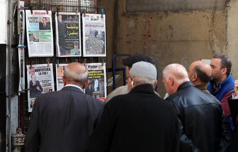 Inwoners van Algiers bekijken kranten met het nieuws van het aftreden van president Bouteflika. Beeld null