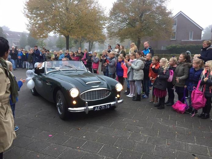 Juf Marijke arriveert in een klassieke sportwagen.