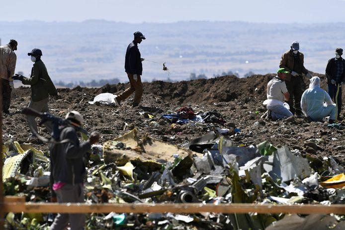 Na de crash in Ethiopië ruimen enkele mensen puin.