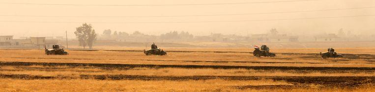 Iraakse troepen rijden voorbij Topzawa. Beeld REUTERS
