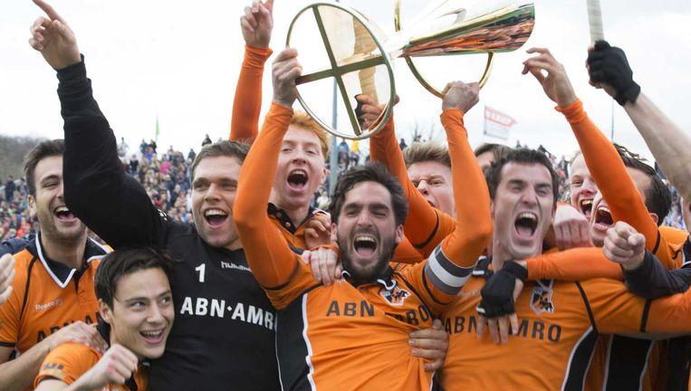 De spelers van Oranje Zwart met Thomas Briels (L), keeper Vincent Vanasch (2L), aanvoerder Robert van der Horst met de beker en Marcel Balkestein (R) vieren het winnen van de Euro Hockey League 2015. Beeld ANP