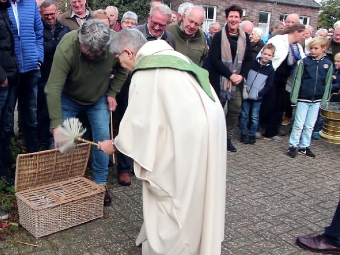 Pastor Mia Tankink zegent de duiven van een Hoevese duivenmelker na afloop van de Hubertusviering.